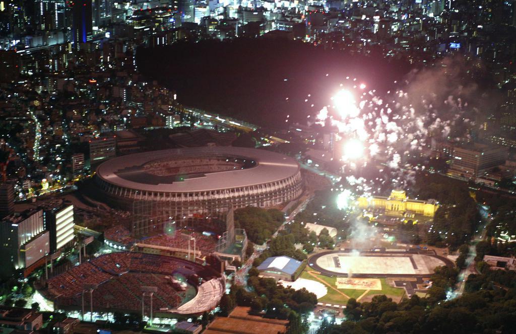 東京の神宮外苑花火大会で打ち上がる花火と照らし出された新国立競技場(中央)=10日夜