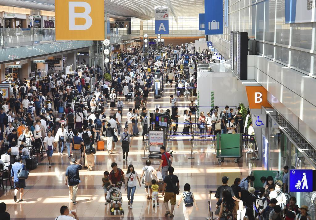 お盆の帰省客らで混雑する羽田空港国内線ターミナル=10日午後