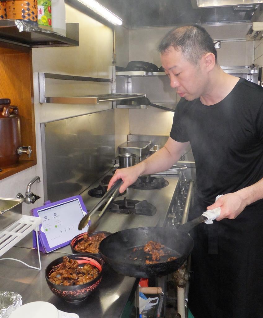 タブレットがモバイルオーダーの注文を通知。調理の手を止めることなく対応できる=東京都文京区の「どんぶり豚三」