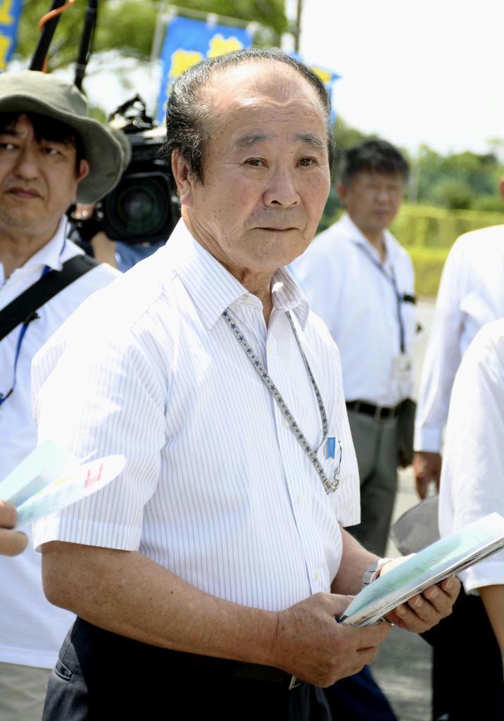 市川修一さんが拉致された海岸付近で、ドライバーらに情報提供を呼び掛ける兄の健一さん