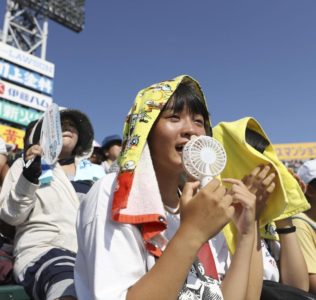強烈な日差しの中、全国高校野球選手権大会を観戦する人たち=11日午後、甲子園球場
