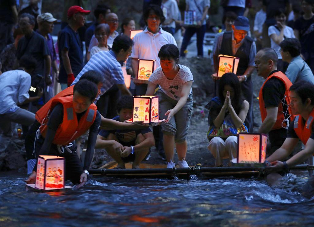 日航ジャンボ機墜落事故から12日で34年となるのを前に「御巣鷹の尾根」の麓の神流川に灯籠を流す人たち=11日夕、群馬県上野村