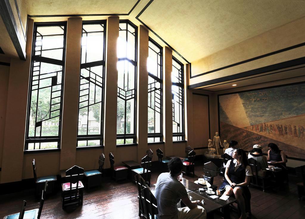 幾何学模様が優雅なホールの大窓。ライトは、限られた予算のなかでも意匠を凝らすことにこだわった=東京都豊島区