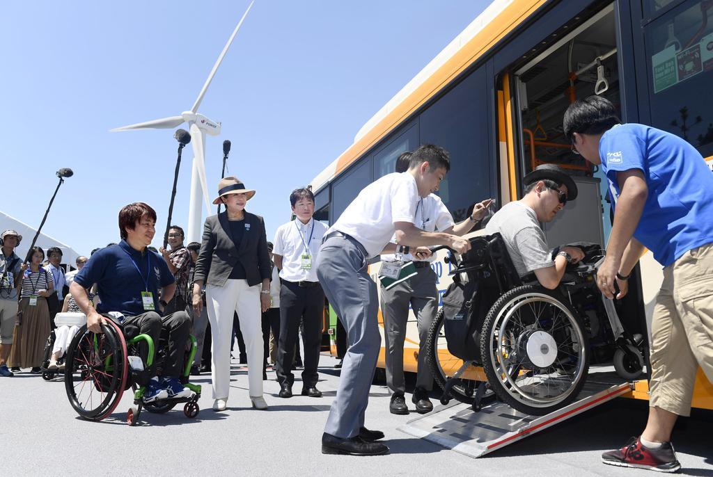 車いす利用者がバスから降りる様子を見る東京都の小池百合子知事(左から2人目)=11日、海の森水上競技場