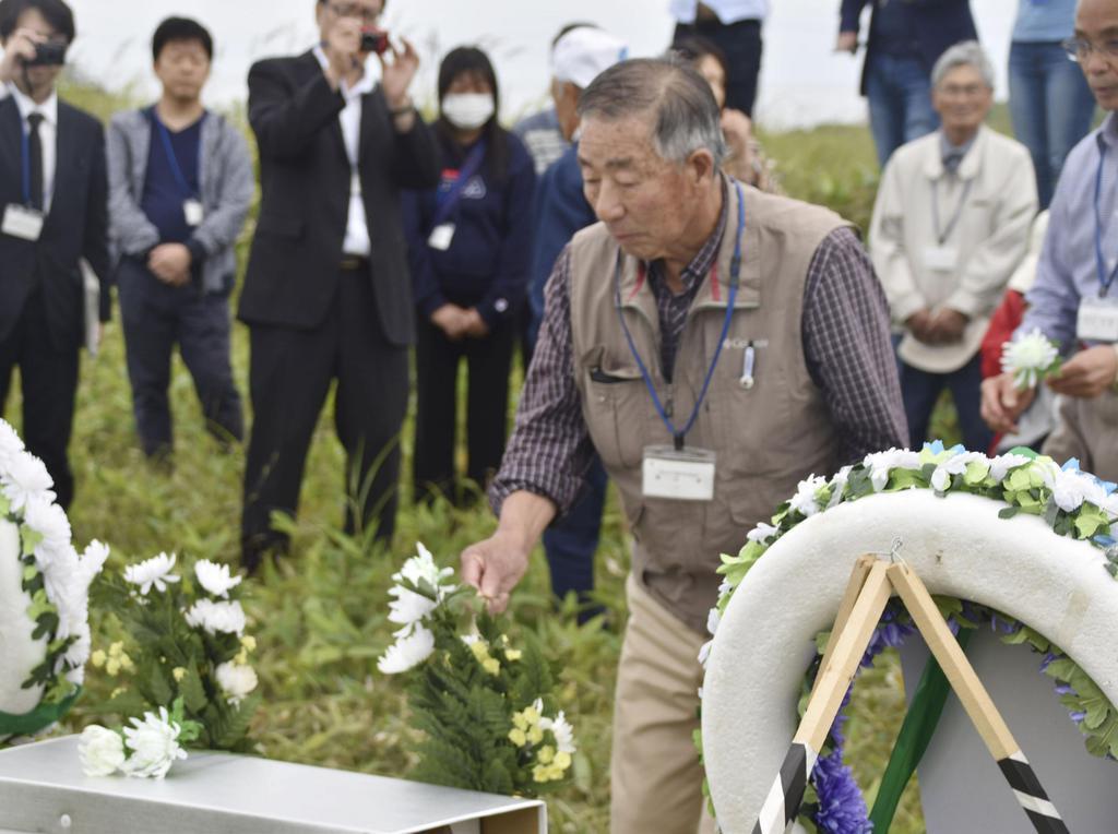 北方領土・国後島の泊墓地での慰霊式で献花する墓参団員=10日