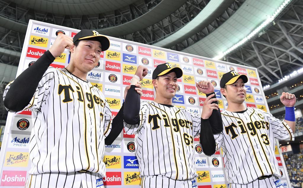 広島に勝利し、お立ち台でポーズをとる(左から)阪神・大山、植田、糸原=京セラドーム