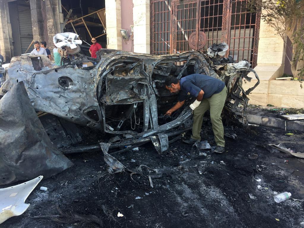 自動車爆弾が爆発した場所を調べる警備員=10日、リビアのベンガジ(ロイター)