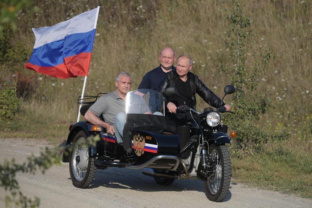 ウクライナ南部クリミア半島でバイク愛好家らと共に疾走するロシアのプーチン大統領=10日、セバストポリ(スプートニク提供・AP)