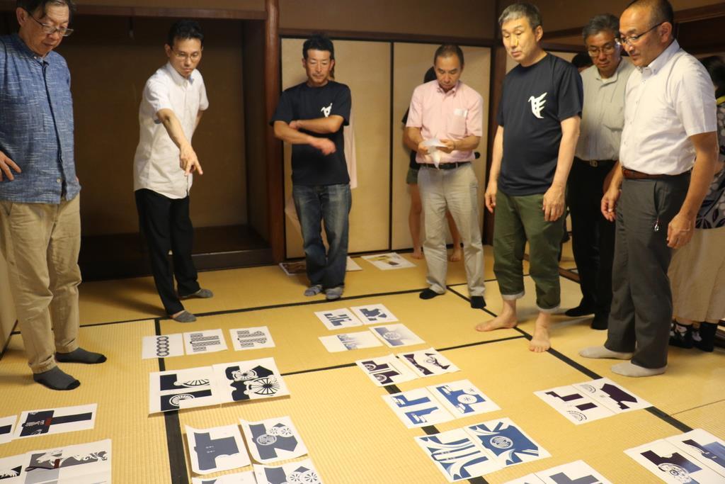 並べられた様々な浴衣のデザインから投票する作品を選ぶ鷹山保存会のメンバー=京都市中京区
