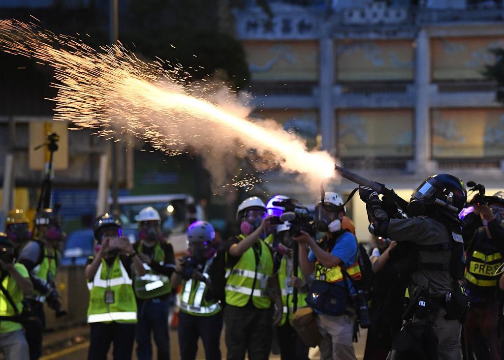 香港中心部で、デモ隊に向け催涙弾を発射する警官隊=11日(共同)