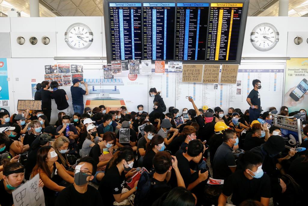 12日、香港国際空港の出発ホールに集まる抗議活動の参加者(ロイター)