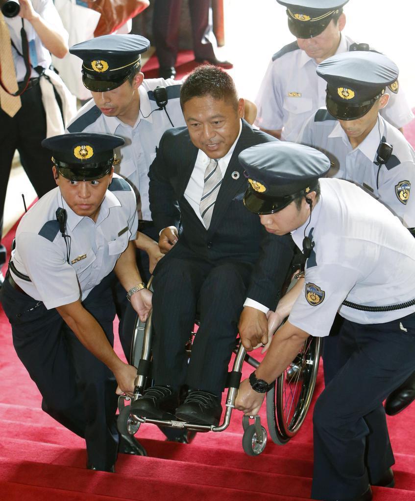 国会議事堂の階段で車いすを持ち上げられ、初登院する国民民主党の横沢高徳氏=8月1日