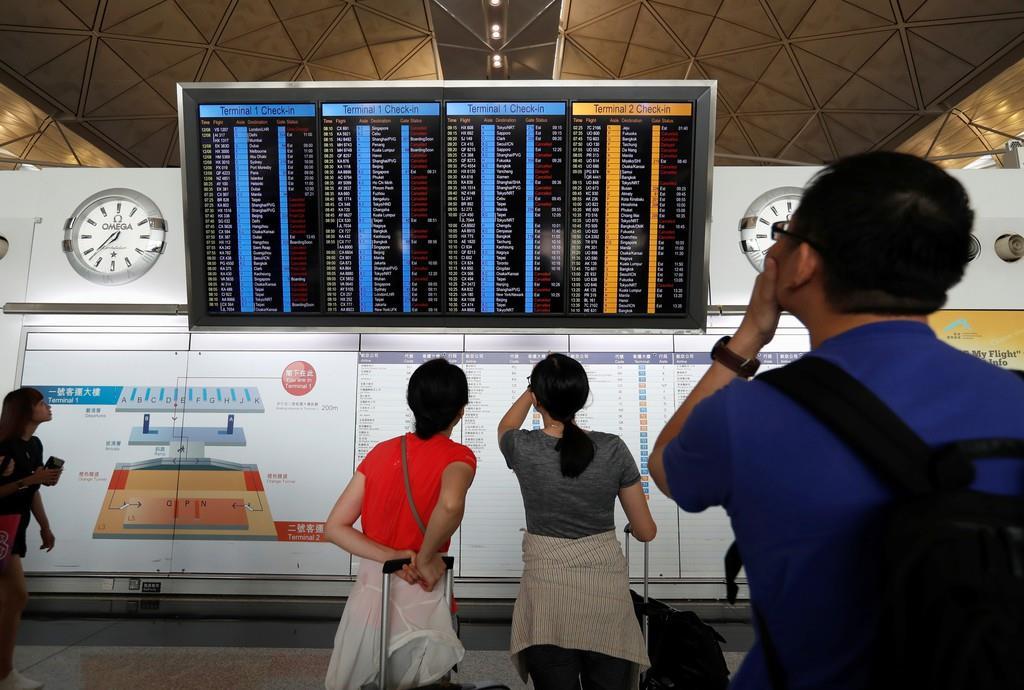 旅客機の発着予定を確認する搭乗客=13日、香港(ロイター)
