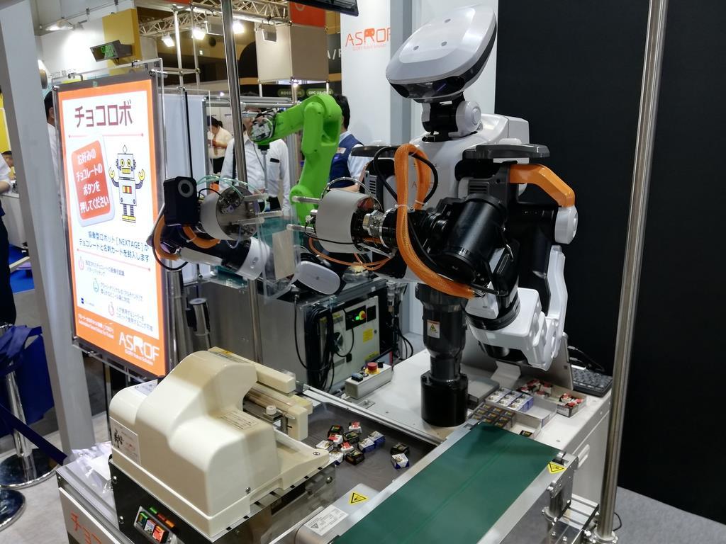 なめらかな動きで名刺とチョコレートを封入するロボット=6月、大阪市住之江区のインテックス大阪
