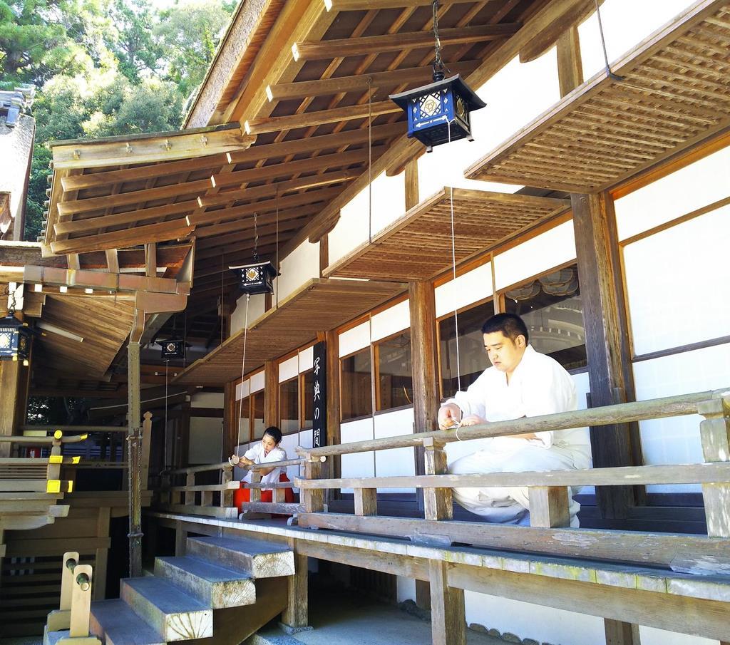 燈籠をひもで固定し、台風の接近に備える神職ら=奈良県桜井市の大神神社
