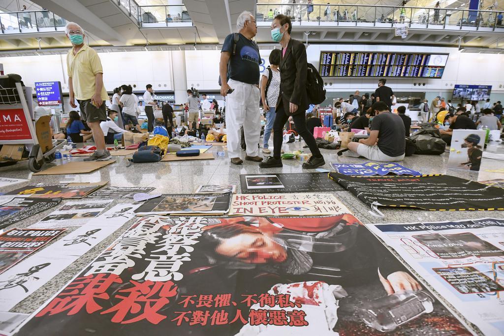 香港国際空港の到着ゲート前の床に張られた警察を批判するポスター=14日(共同)