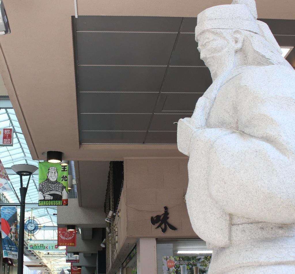 関羽の石像(右手前)と三国志の武将のイラストが描かれた旗=神戸市長田区