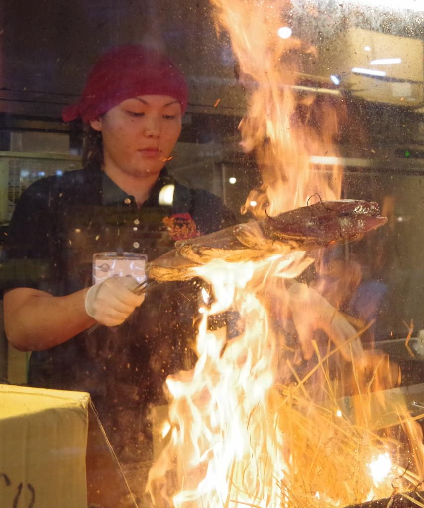ひろめ市場では、目の前でわら焼きにしたカツオのたたきを食べることができる=高知市