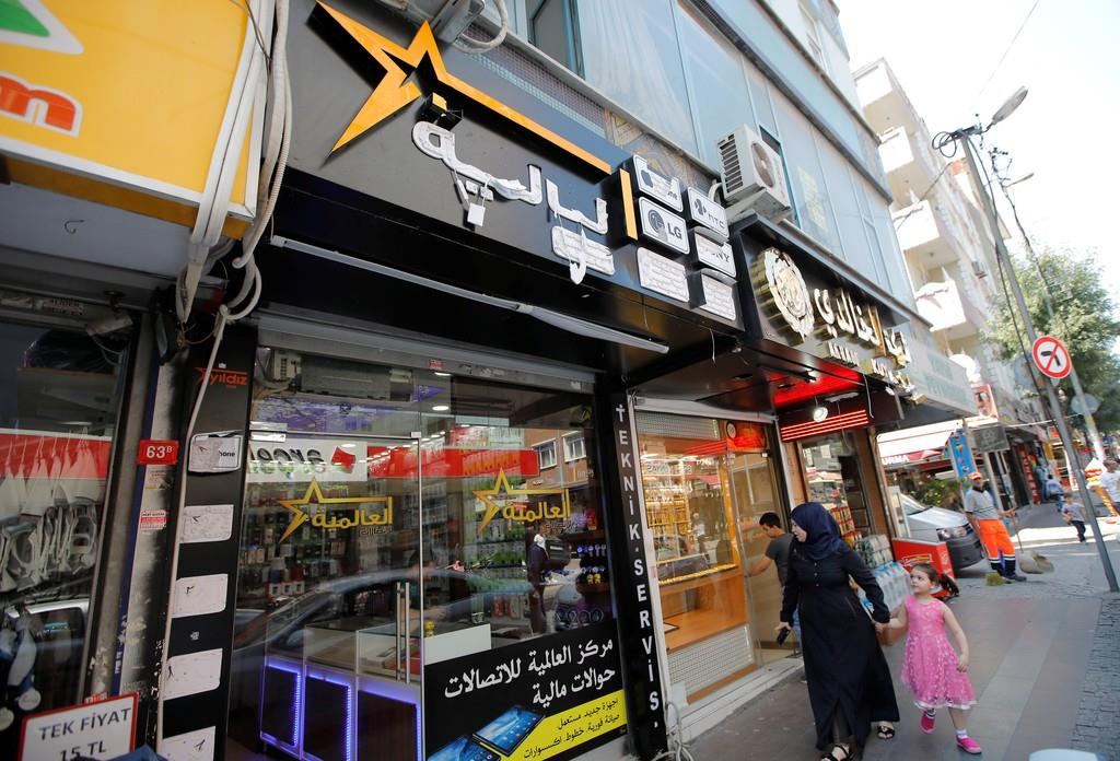 アラビア語の看板を掲げるイスタンブールの電器店(ロイター)。シリア難民の流入・定着でこうした店舗が増えたことも、地元の反感につながっている