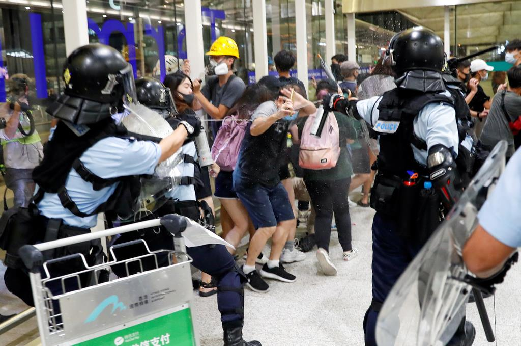 デモ隊に対し、警官隊は催涙スプレーを使うなどした=13日、香港国際空港(ロイター)