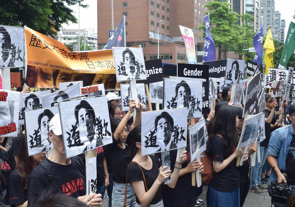 14日、台北市内の日本台湾交流協会の事務所前で、安倍晋三首相に謝罪を求めるプラカードを掲げる抗議活動の参加者ら(田中靖人撮影)