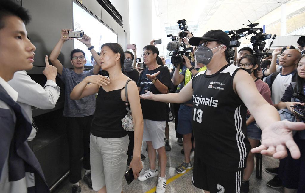香港国際空港で、ターミナルへの入場が規制されたことを関係者(左側)に抗議する人たち=14日(共同)