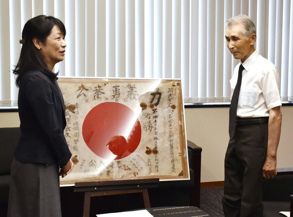 福井県大野市の石山志保市長(左)に日章旗の返還を報告する遺族の石田治さん=14日午前