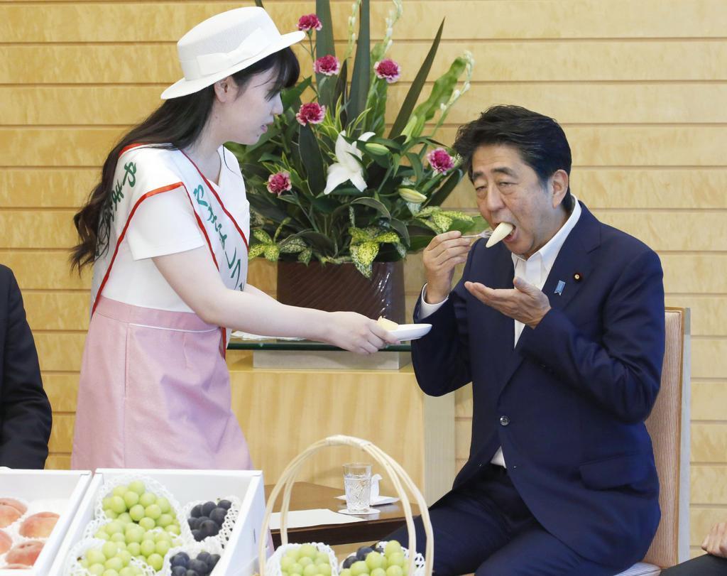 山梨のモモを試食する安倍晋三首相。日本産のモモは海外の評価が高い=8月5日