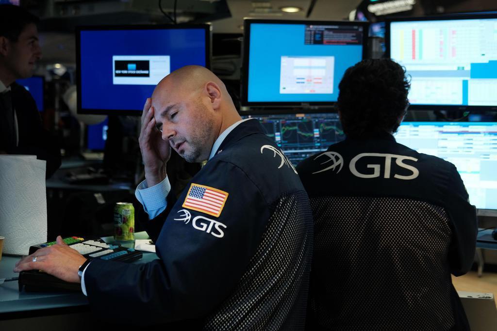 14日、ニューヨーク証券取引所のトレーダーら(ゲッティ=共同)