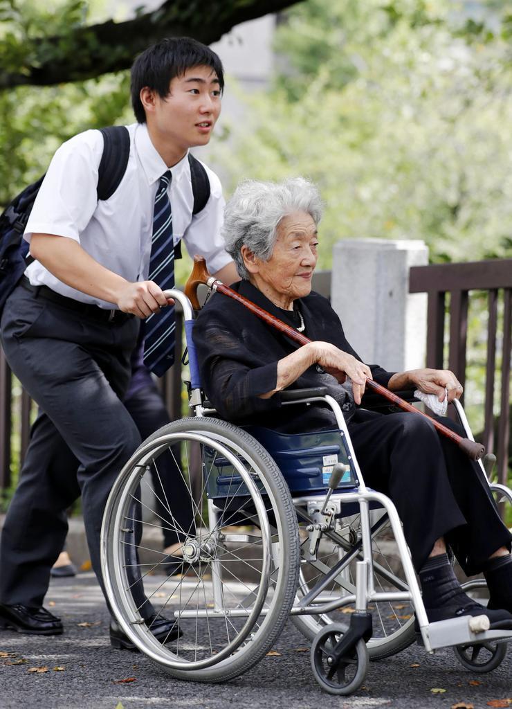 全国戦没者追悼式に向かう参列遺族の最年長者の内田ハルさん。左はひ孫の広沢駿さん=15日午前、東京・日本武道館