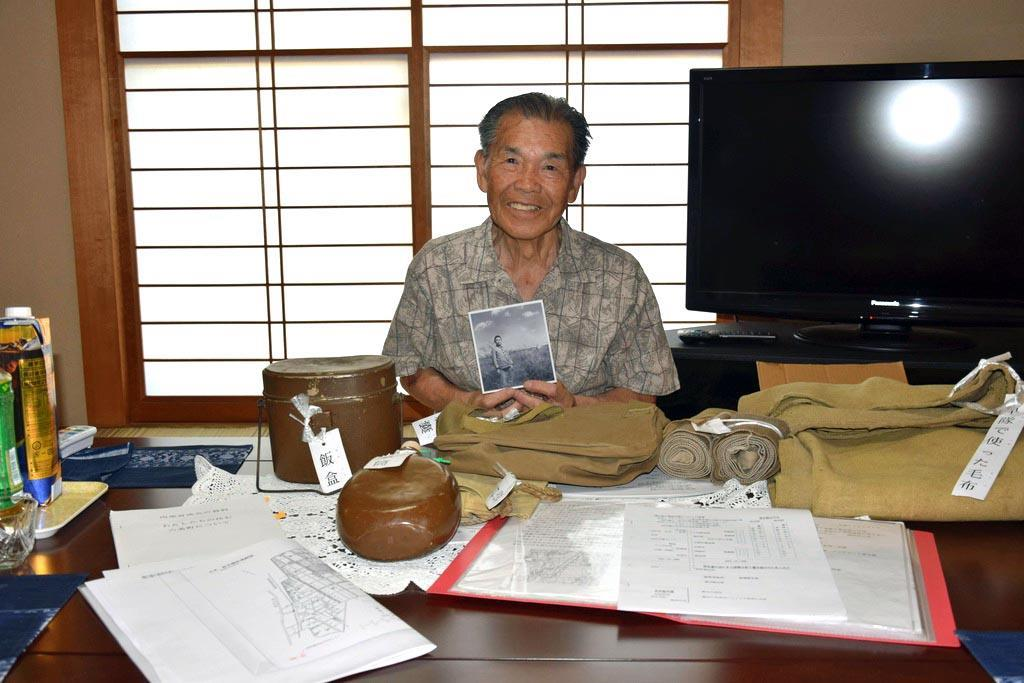 軍用機を背景に撮影した写真を手にする岩田さん=壬生町壬生丁