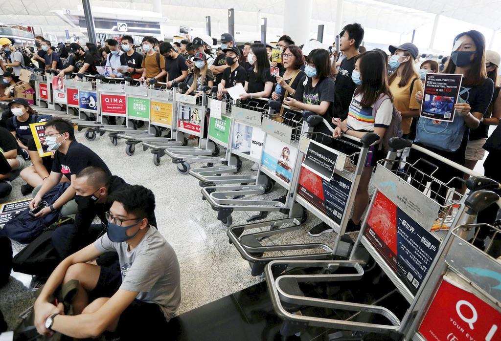 「逃亡犯条例」改正案を巡り、香港国際空港でカートを使いバリケードを作るデモ隊=13日(ロイター)