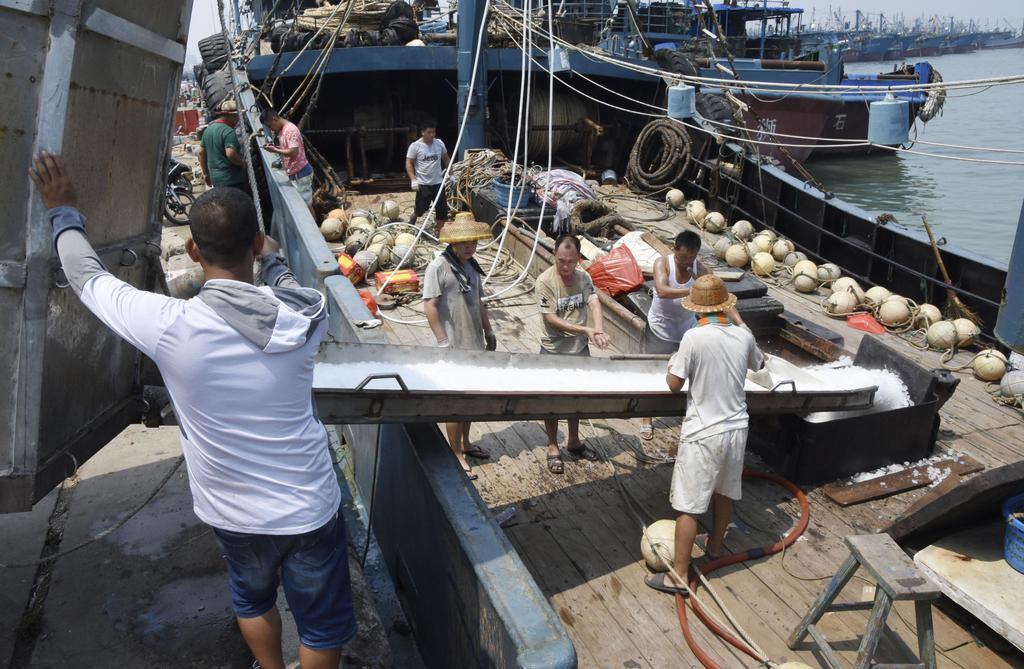 出港準備のため漁船に氷を積み込む漁師ら=15日、中国福建省石獅市(共同)