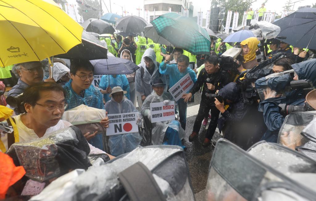 日本大使館の入った建物前までデモ行進をした参加者=15日、ソウル