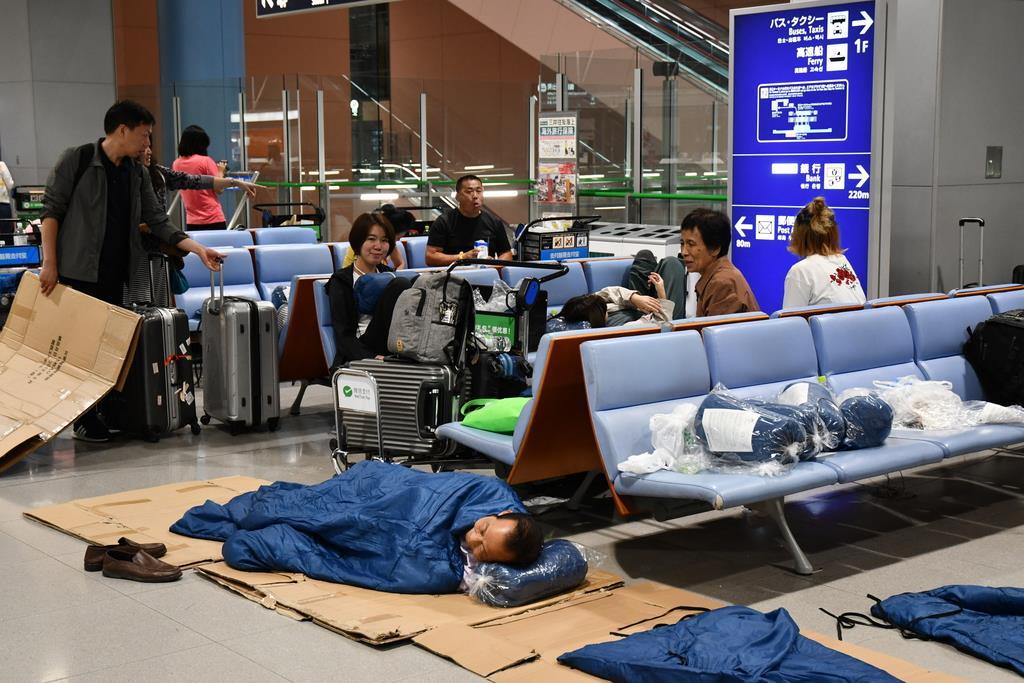 ターミナルの床に寝袋を敷いて就寝する利用客=15日夜、関西国際空港