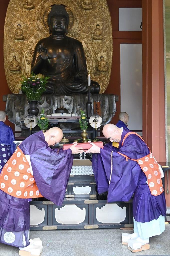 仏前で鍵を引き継ぐ加藤朝胤師(右)=奈良市の薬師寺