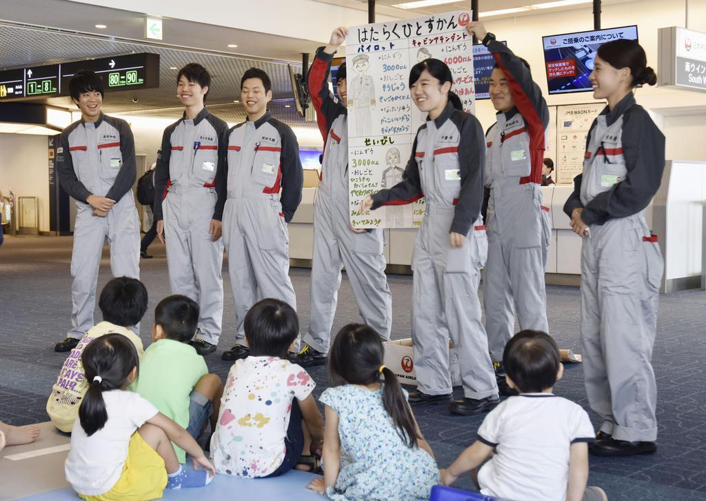 搭乗前の子供たちに「飛行機のイロハ」を解説する日航の新人整備士=2日午前、羽田空港