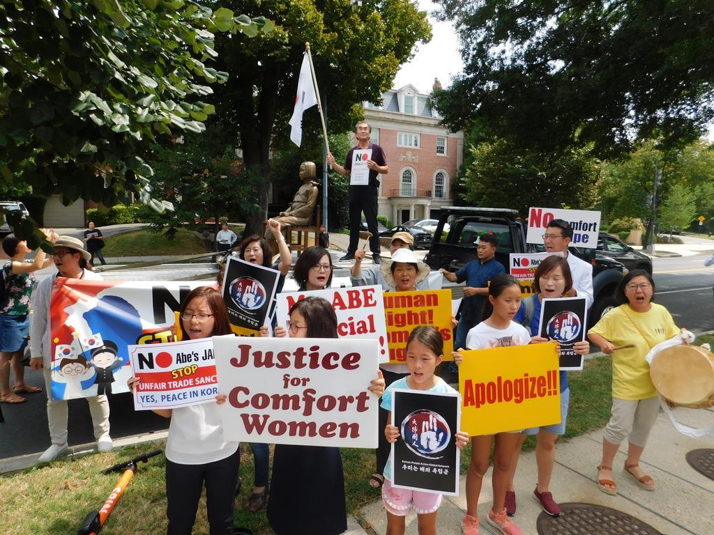 米ワシントンの日本大使館前で、トラックに載せた慰安婦像とともに抗議活動を行う韓国系団体の人々=15日