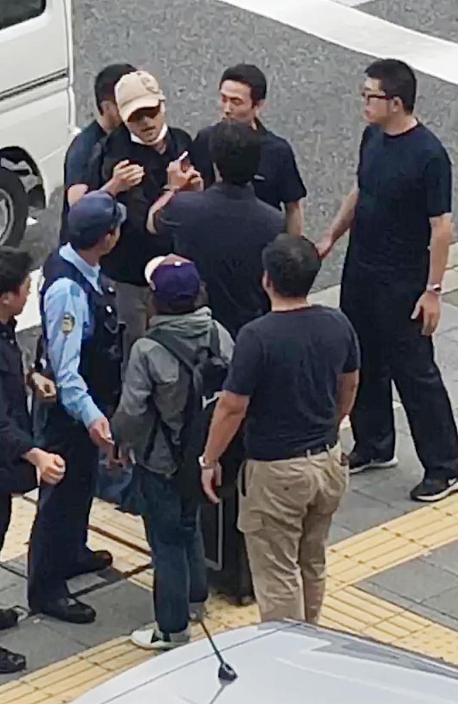 大阪市内で警察官に囲まれる、宮崎文夫容疑者(ベージュの帽子)=18日午前、大阪市東住吉区(近隣住民提供)