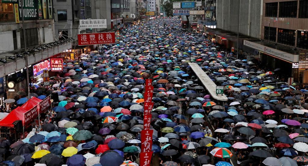 香港中心部の道路でデモ行進する抗議集会の参加者ら=18日(ロイター)
