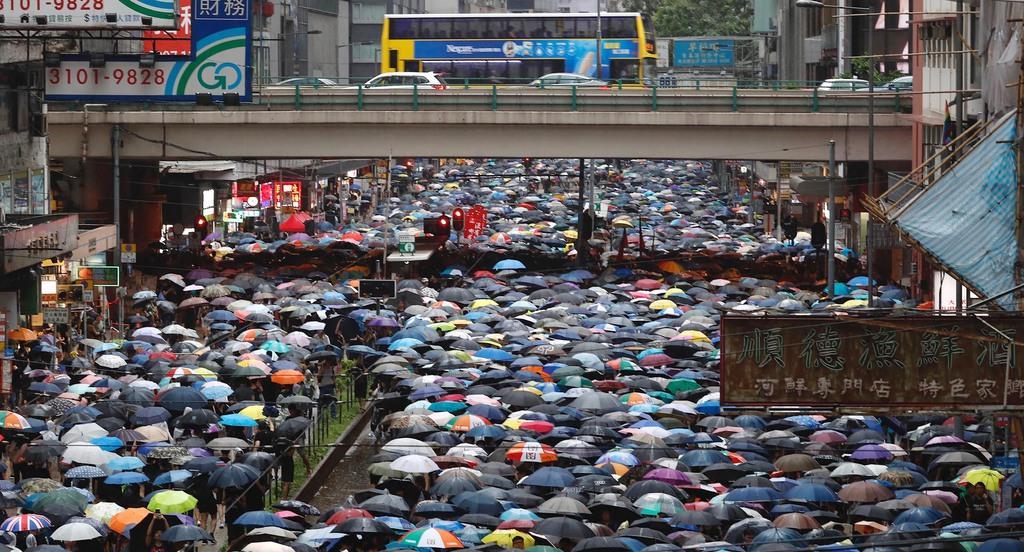 香港中心部の道路でデモ行進する抗議集会の参加者ら=18日(AP)