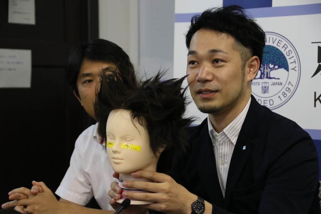 マネキンを手に、新開発の整髪技術について説明するマンダムの占部駿主事(右)=京都市左京区