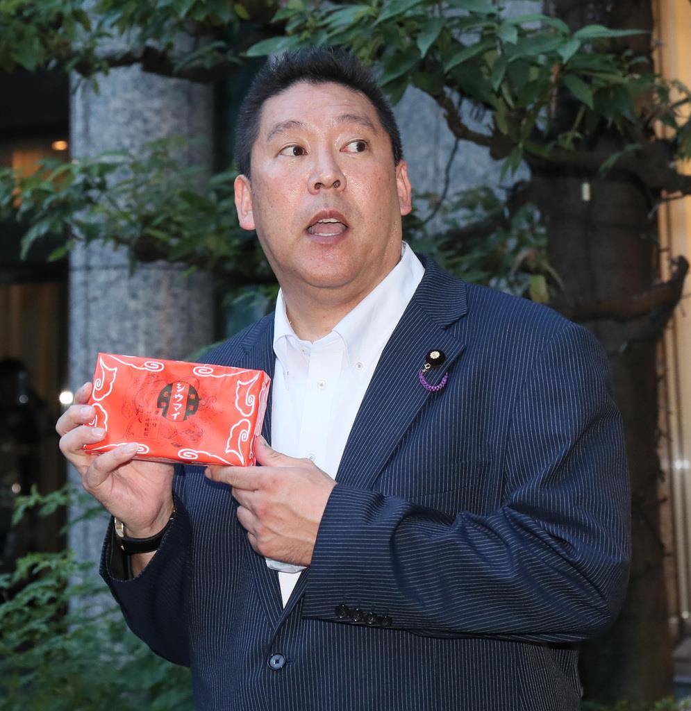 TOKYO-MX前で、崎陽軒の箱を手に話をする、NHKから国民を守る党の党首、立花孝志氏 = 東京・麹町 (撮影・中井誠)