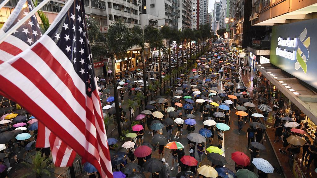 「逃亡犯条例」改正案の撤回などを求めるデモの参加者と街頭に掲げられた星条旗=18日、香港(共同)