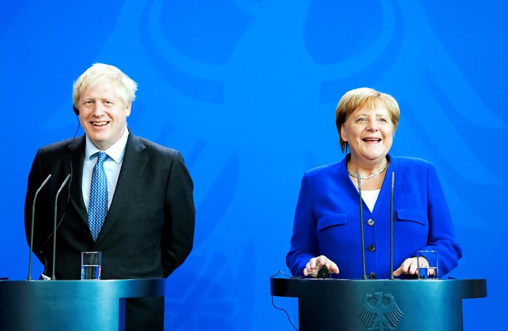 笑顔で会見に臨むジョンソン英首相(左)とメルケル独首相=21日、ベルリン(ロイター)