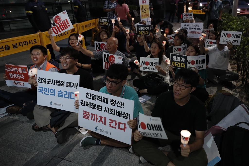 韓国政府による日韓の軍事情報包括保護協定(GSOMIA)破棄の報を受け、歓迎するデモ参加者たち=22日、ソウルの日本大使館前(AP)