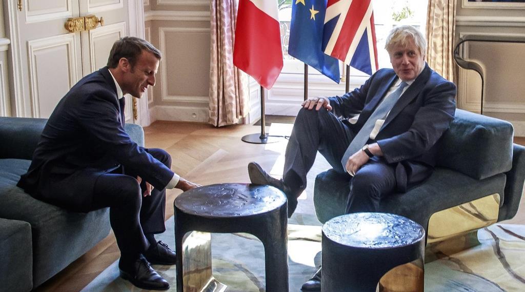 フランスのマクロン大統領(左)と会談する英国のジョンソン首相=22日、パリのエリゼ宮(AP)