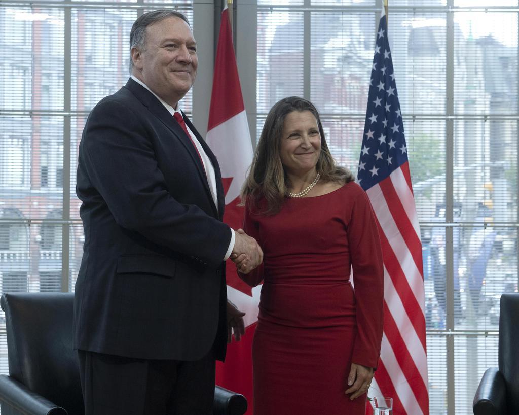 握手するフリーランド外相(右)とポンペオ米国務長官=22日、カナダの首都オタワ(ADRIAN WYLD/THE CANADIAN PRESS提供・AP=共同)