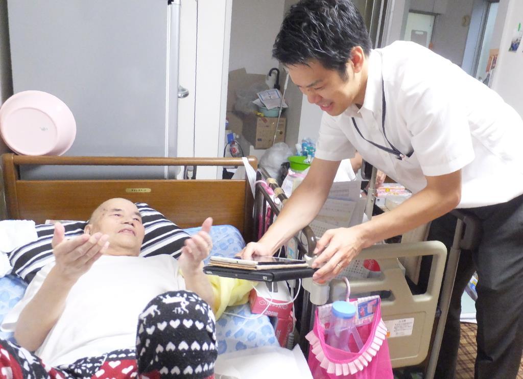 患者の要望や心配事などを聞き出す在宅医療PAの木村圭佑さん(右)=東京都新宿区