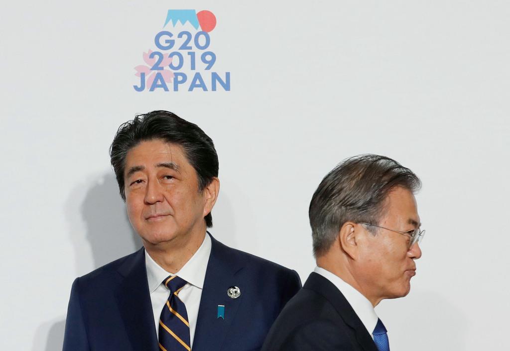 6月、G20大阪サミットで握手した後、すれ違う韓国の文在寅大統領(右)と安倍首相=大阪市(ロイター)